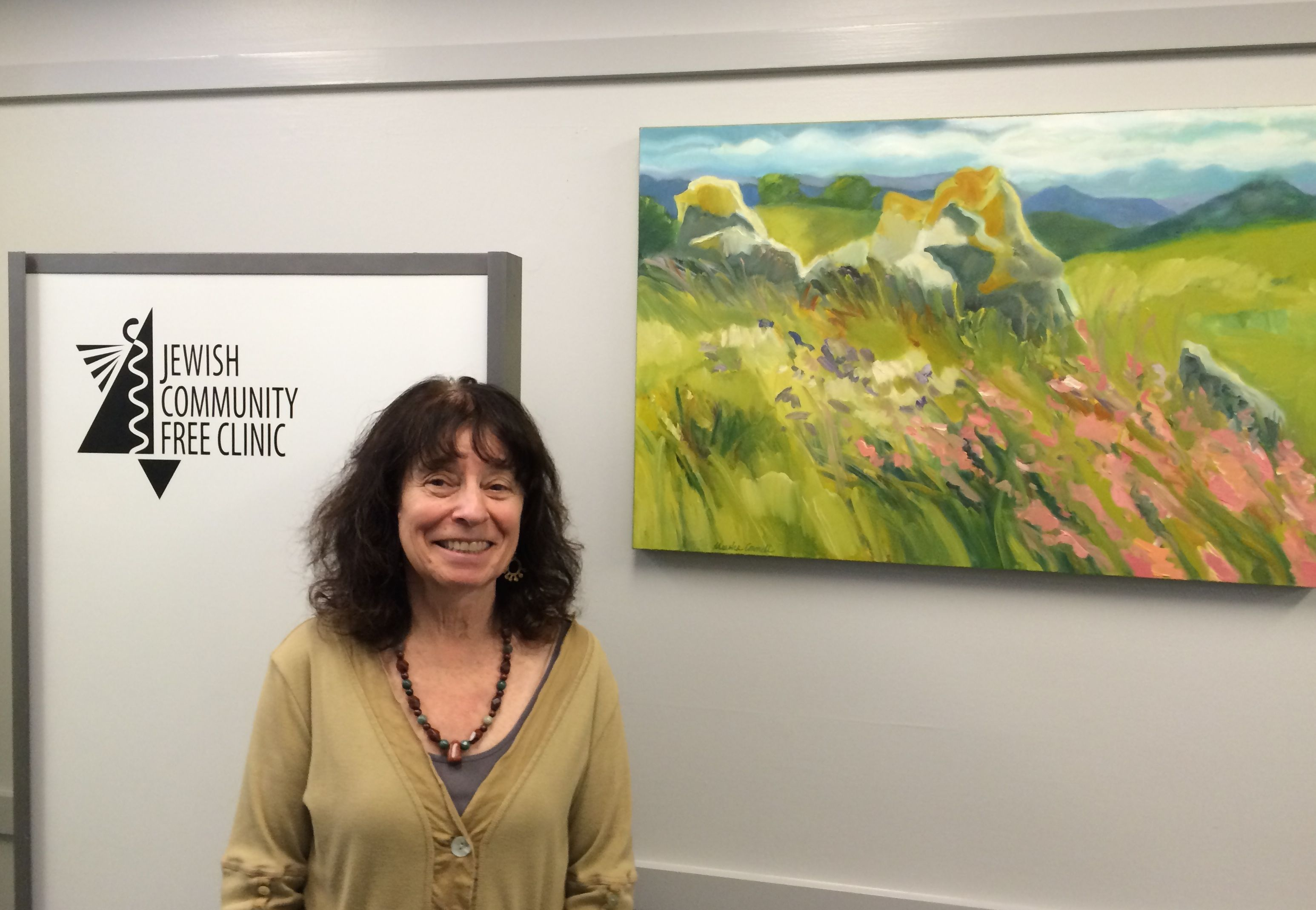 Marsha Connell with one of her oil paintings, Mallows and More—Pepperwood Preserve, donated to Jewish Community Free Clinic.
